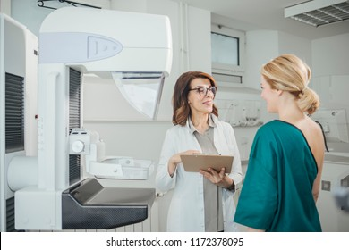 Woman oncologist talking with her patient on mammography examination.