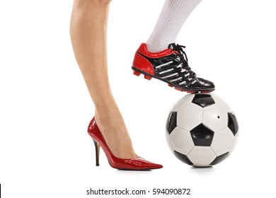Woman with one foot in a high-heeled shoe and other in a soccer shoe pressing a football isolated on white background