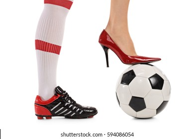 Woman with one foot in a soccer shoe and other in a high-heeled shoe pressing a football isolated on white background
