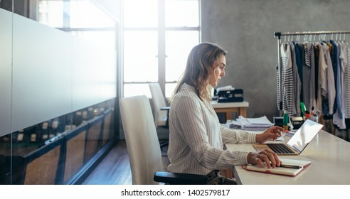 Woman online entrepreneur working on laptop at office. ecommerce business owner working at her desk.