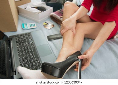 woman online shopping trying new shoes on her sexy long legs. concept of e-commerce using laptop on bed