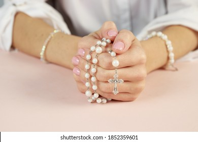 Woman only closeup of hands to be seen with rosary sending a prayer to God, The girl prays for peace and for overcoming the pandemic in the world.