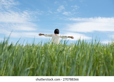 Woman with open arms in green field