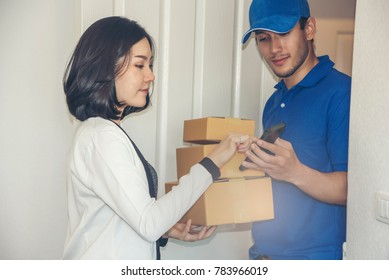 Woman open the door and hand accepting a delivery of boxes from deliveryman
