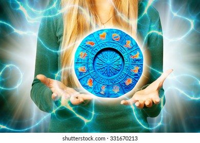 woman with open hands holding a zodiac plate with astrology signs