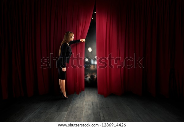 Woman open red curtains of the theater stage