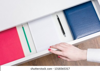 Woman open shelf with notebooks and pens, top view, background, copy space, advertising