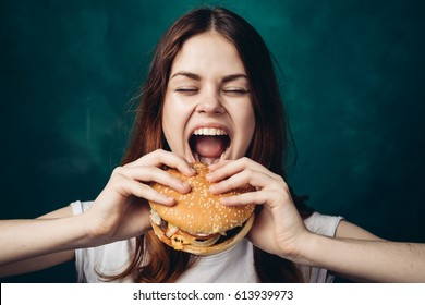 The woman opened her mouth to eat a hamburger, a hamburger in her hands, a woman with a hamburger