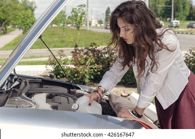 Woman opened the hood and she pours liquid glass washer. Concept: a road accident, car service