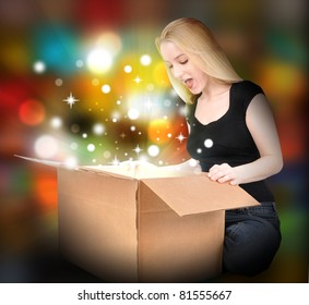 A woman is opening a box with a present inside. Sparkles and glowing are around her. Use it for a Christmas or Birthday concept.