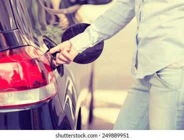 Woman opening car gas tank cap at petrol station