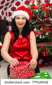 Woman opening Christmas gift in front of Xmas decorated  tree
