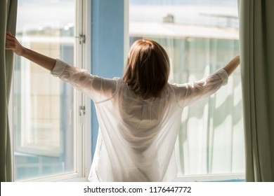 woman opening curtains in the bedroom in the morning