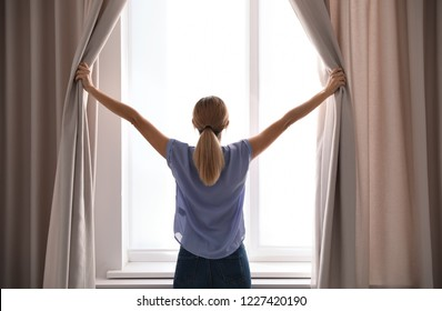 Woman opening curtains and looking out of window at home