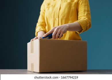 Woman opening a delivery box using a cutter