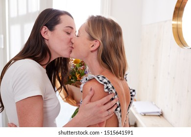 Woman Opening Front Door To Gay Partner At Home Who Gives Her Bunch Of Flowers