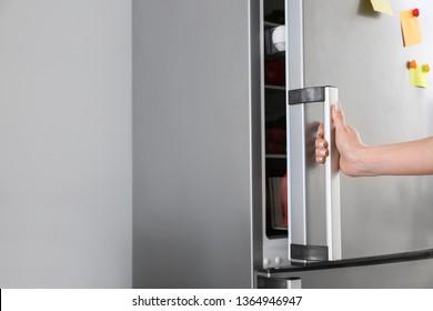 Woman opening modern fridge