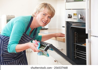 Woman Opening Oven Door And Looking Frustrated