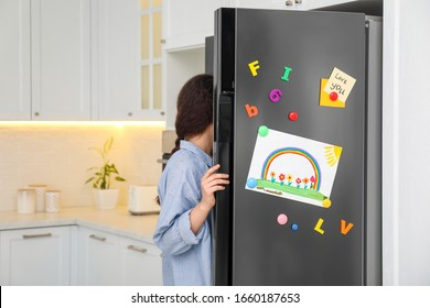 Woman opening refrigerator door with child's drawing, notes and magnets in kitchen