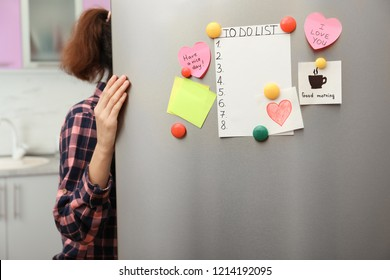 Woman opening refrigerator door with paper sheets and magnets at home, closeup