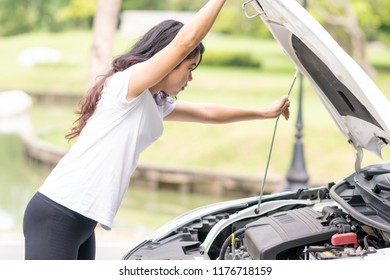 Woman is opening their car skirts to check engines.
