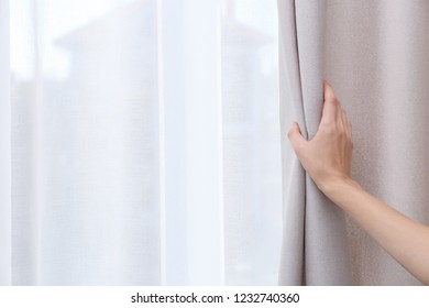 Woman opening window curtains at home, closeup. Space for text