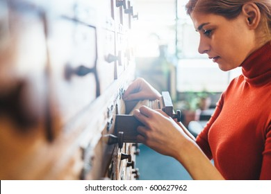 Woman opens database drawer. Young librarian opens library card index. Archive, database, library concept