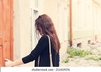 woman opens the door outside portrait