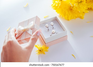 Woman opens a gift box with a set of pearl jewellery with yellow flowers