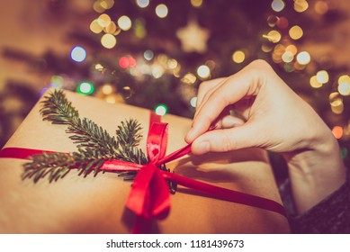 Woman opens a gift on christmas tree lights blurry background. Detail of hand and present box with red ribbon. Xmas celebration and holiday mood.