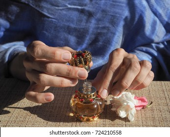 A woman opens the perfume oil. Scented oil in women's wrists. Arabian perfume oil.