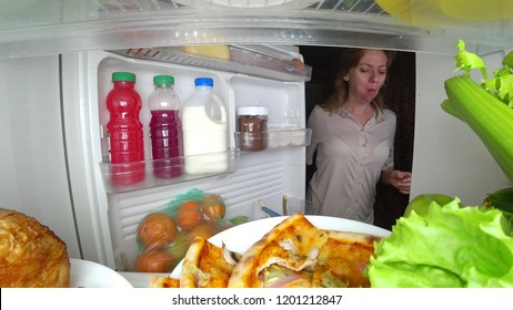Woman opens the refrigerator at night. night hunger. diet gluttony