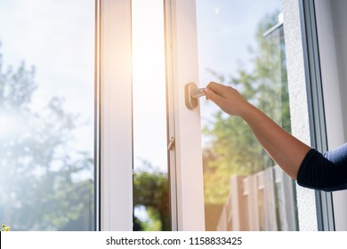 woman opens a window with a mosquito net