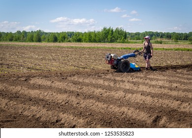 woman operation a rototiller tractor unit on the farmland field