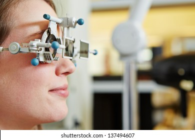 Woman at optician with trial frame and trial glasses for lens determination