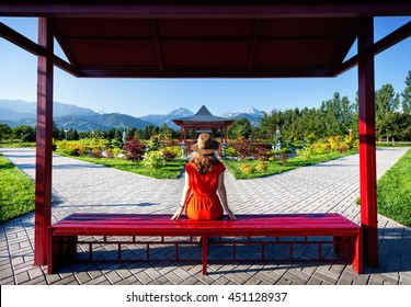 Woman in orange dress and hat sitting on the bench near pagoda in Japanese Garden