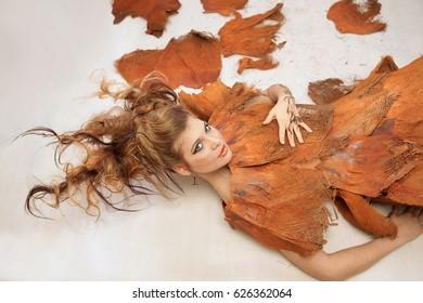 Woman in an orange fancy outfit, lying down, fashion, studio
