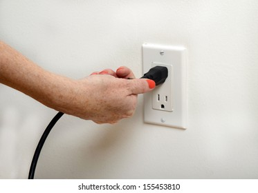 woman with orange fingernails pulling the plug