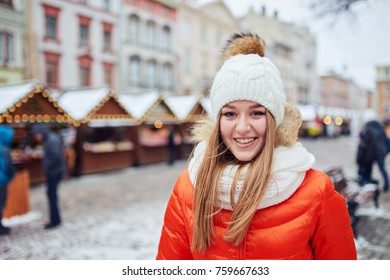 A woman in orange jacket on background of a winter city