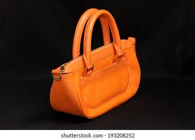 Woman orange leather handbag isolated black background