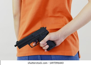 Woman with orange shirt is holding black gun on white isolated background