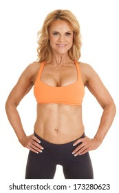 A woman in an orange sports bra with her hands on her hips.