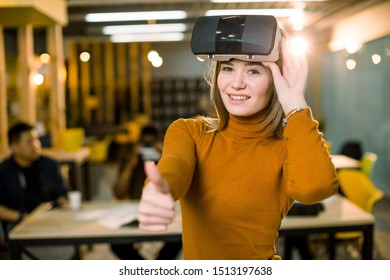 Woman in orange sweater and jeans wearing VR goggles watched by her multiethnical colleagues in modern office