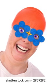 Woman with an orange swim cap and blue spring flower eye glasses making a funny face isolated over white