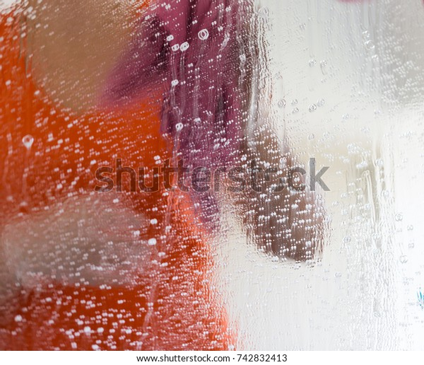 Woman in orange t-shirt cleaning a mirror. Inarticulate body view through detergent splashes and stains. Close up square crop