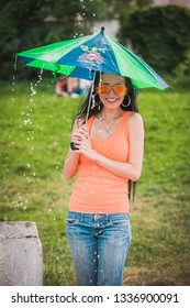 woman in orange t-shirt with kid umbrella under rain in summer