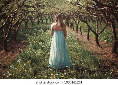 Woman in an orchard with flowers. Paint like effect