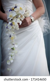 Woman with orchid bridal bouquet and white wedding dress