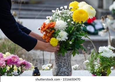 Woman organize flowers in a vase on a tombstone - all souls day preparing in the cemetery