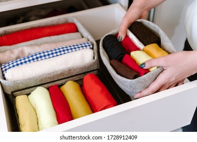 Woman organizing clothes in wardrobe, putting stuff in boxes, baskets into shelves and drawer. Concept of minimalism lifestyle and japanese t-shirt folding system. Tidy up closet